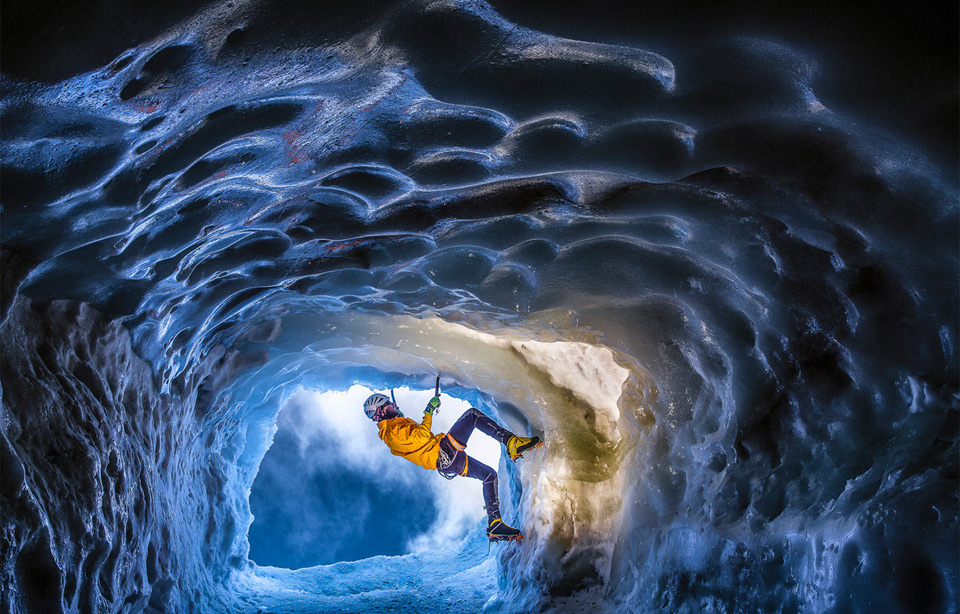Climbing climbing in a glacial ice cave in the alps