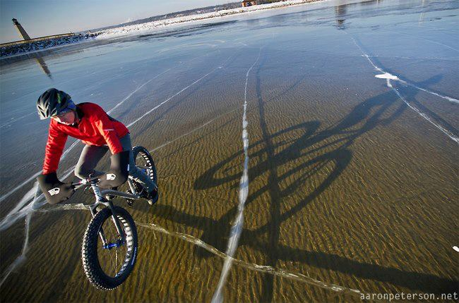 MTB Winter cycling on Lake Michigan ice so clear it almost looks like he's floating