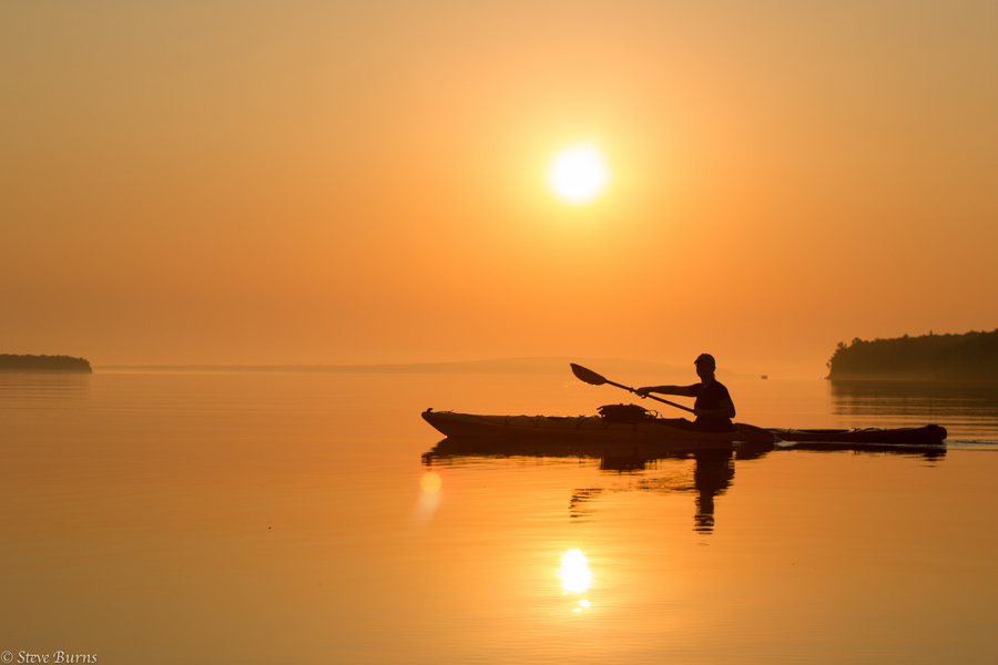 Kayak and Canoe Paddling through the mist early in the morning on Lake Superior in the Apostle Islands