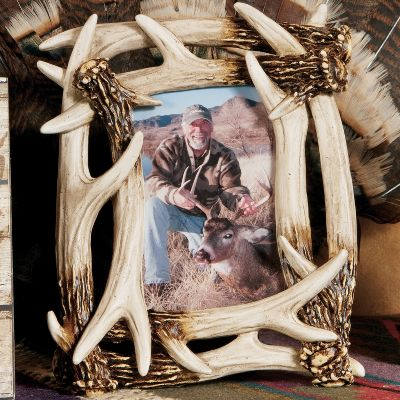 Add some rustic charm to your home or cabin, and display your favorite memories with this high-quality, nature-inspired picture frame. Frame holds one 4 x 6 photo and boasts beautiful poly-resin antler accents. Imported. - $12.99