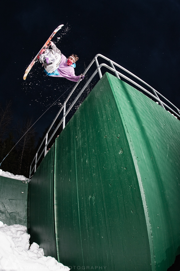 Ski Leigh Powis handplants on a railing as he jumps off the roof of a building on his skis