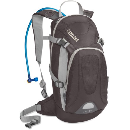 Camp and Hike Slim fitting for trail running and trail riding, the women-specific CamelBak L.U.X.E. hydration pack offers a comfortable fit, 100 fl. oz. reservoir and plently of room for your essentials. 100 fl. oz. Antidote(TM) reservoir has its own compartment and is equipped with the Quick Link(TM) connection system for hassle-free removal of the drinking tube. Quick Link system also lets you effortlessly add accessories such as a Fresh(TM) filter, insulated tube, tube director or flow meter (accessories not included). Big Bite(TM) valve is ergonomically positioned for easy drinking; valve securely shuts off water flow with an easy, quick turn. Women-specific design includes a narrow, curved shoulder harness, slider sternum strap and short back length to maximize comfort; hipbelt is removable. Air Director(TM) ventilated back panel and mesh shoulder straps offer cooling airflow and quick-drying performance. Main compartment, front zippered pocket with internal organization and lined top, and zippered media pocket all store and organize gear. Expandable scoop pocket holds extra gear. CamelBak L.U.X.E. hydration pack has reflective detailing that increases your visibility in low light. Closeout. - $69.73