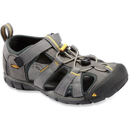 Surf The Keen Seacamp CNX sandals for kids feature a low-profile, minimalist design that won't weigh them down while on the move. Washable polyester webbing wraps feet comfortably; patented toe guards protect feet and uppers. Elastic cord laces secure with cordlocks for slip-on ease and a comfortable, easily adjustable fit. Contoured EVA topsoles feature molded arches for light support. Thin EVA midsoles encourage natural movement while offering light cushioning underfoot. Nonmarking rubber outsoles on the Keen Seacamp CNX sandals feature multidirectional flex grooves and razor siping for enhanced traction on slick surfaces. Please note: as part of the Keen CNX line, these sandals have a slightly reduced width and volume compared to regular Keen sandals, providing a better-connected fit. - $26.83