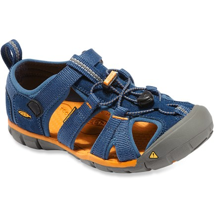 Fitness The kid's Keen Seacamp CNX sandals offer a low-profile, minimalist design that won't weigh them down while they splash through creeks or run around the playground. Washable polyester webbing wraps feet comfortably; patented toe guards protect feet and uppers. Elastic cord laces secure with cordlocks for slip-on ease and a comfortable, easily adjustable fit. Contoured EVA topsoles feature molded arches for light support. Thin EVA midsoles encourage natural movement while offering light cushioning underfoot. Nonmarking rubber outsoles on the Keen Seacamp CNX sandals feature multidirectional flex grooves for enhanced traction on slick surfaces. Please note: as part of the Keen CNX line, these sandals have a slightly reduced width and volume compared to regular Keen sandals, providing a better-connected fit. - $26.83