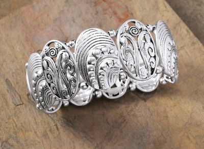 Entertainment Adorn your wrist with fascinating swirls and intricate scroll designs. Brilliant and stretching oval-disc bracelet is made of cast metal. Nickel-free. Stretches up to 7.5. Color: Silver. Gender: Female. Age Group: Adult. - $23.99