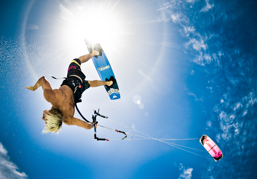Wake Professional kiteboarder, Clinton Bolton doing a handle pass under the midday sun. Caribbean