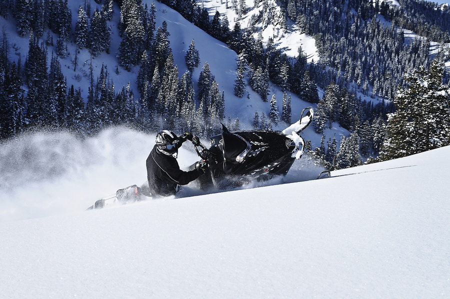 Snowmobile powder turn above the valley