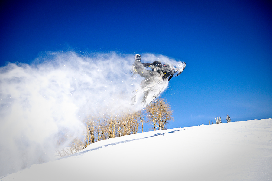 Snowmobile catching air on a blue bird day at Daniels Summit, Utah
