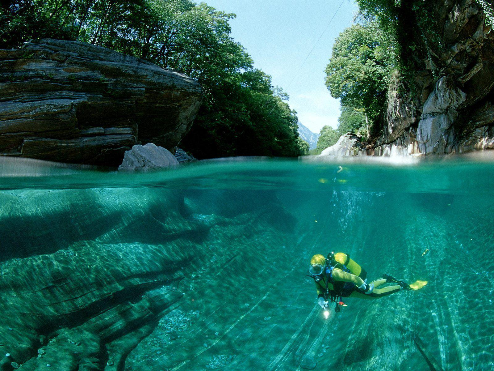 Scuba Awesome split shot of a diver in The Verzasca River, Swiss Alps.