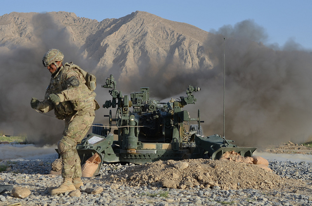Guns and Military Staff Sgt. Freddie Goggins Jr. of Charlie Battery, 1st Battalion, 37th Field Artillery Regiment, 3rd Stryker Brigade Combat Team, 2nd Infantry Division pulls the lanyard and fires a M777 howitzer at Forward Operating Base Al Masaak, southern Afghanistan,