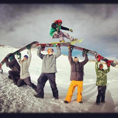 Snowboard Chris Grenier riding over friends