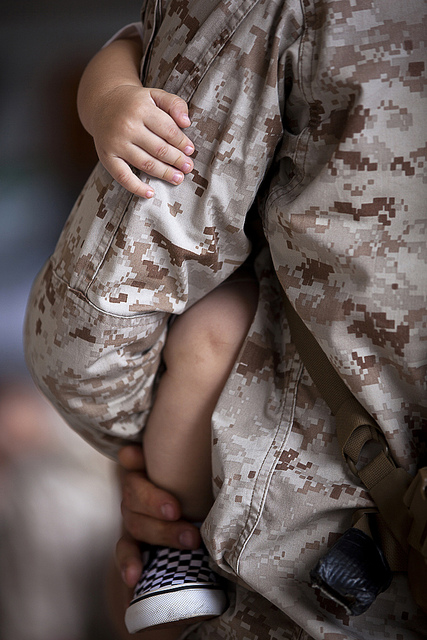Guns and Military Sgt. Jacob Shepherd, a wireman with the 3rd Marine Regiment Embedded Training Team and a 26-year-old native of Bucyrus, Ohio, holds his 1-year-old son closely after returning to Marine Corps Base Hawaii from a seven-month deployment to Afghanistan, Aug. 2