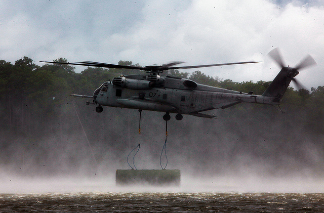Guns and Military A CH-53E Super Stallion with Marine Heavy Helicopter Squadron 366, 2nd Marine Aircraft Wing, drops a section of a raft during a training exercise with 8th Enginner Support Battalion, 2nd Marine Logistics Group, aboard Camp Lejeune, N.C., Aug. 8, 2012.
