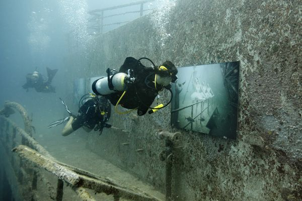 Scuba Divers check out first underwater photo exhibit that was on sunken ship USS Gen. Hoyt S. Vandenberg, located off Key West, Florida.