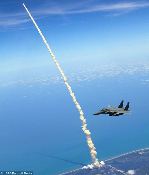 Guns and Military Lt. Col. Gabriel Green and Capt. Zachary Bartoe patrol the airspace in an F-15E Strike Eagle as the Space Shuttle Atlantis launches May 14, 2010, at Kennedy Space Center, Colonel Green is the Fighter Squadron commander and Captain Bartoe is a weapons syst