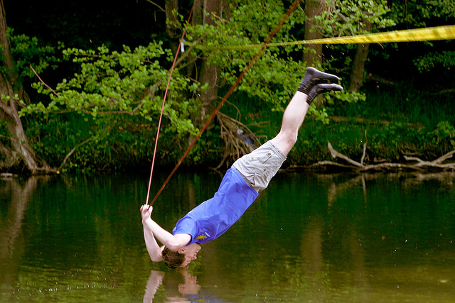 Extreme Slackliner contemplating the nature of gravity and the promising freshness of a small river