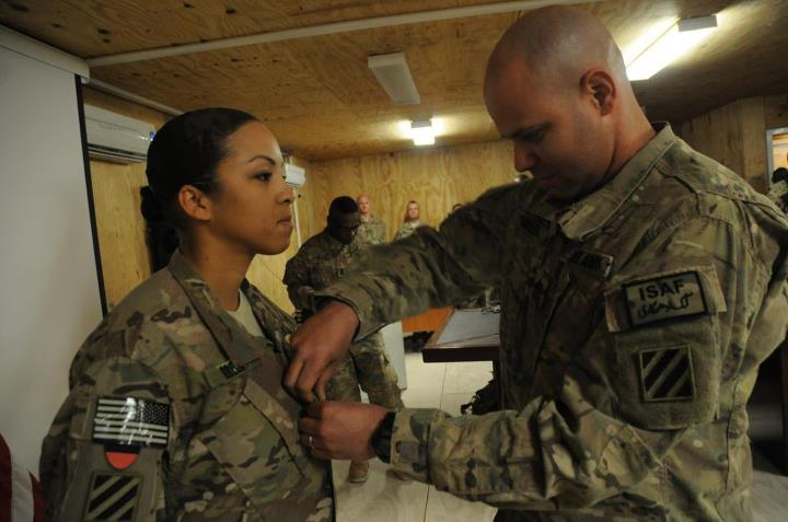 Guns and Military First Sgt. Andre Green, with Company A, 3rd Battalion, 15th Infantry Regiment, 4th Infantry Brigade Combat Team, 3rd Infantry Division promotes his spouse, Tanya Green, public affairs noncommissioned officer in charge with the 3rd Sustainment Brigade, 3rd