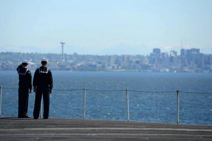Guns and Military Sailors look out at the Seattle skyline from the flight deck aboard the aircraft carrier USS John C. Stennis (CVN 74). John C. Stennis is returning from an eight-month deployment to the U.S. 5th and 7th Fleet areas of responsibility. (U.S. Navy Photo by M