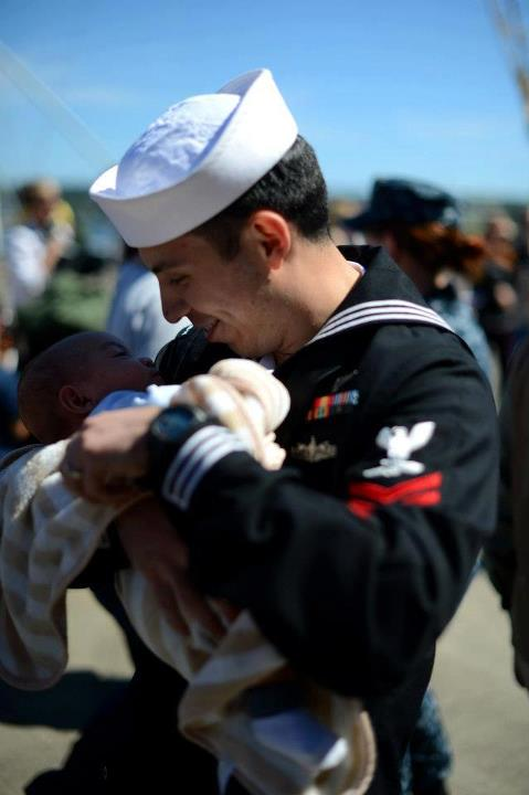 Guns and Military Aviation Boatswain's Mate (Handling) 2nd Class Abel Cholico stationed aboard the aircraft carrier USS John C. Stennis (CVN 74) meets his child for the first time during their homecoming to Naval Station Kitsap in Bremerton, Wash. John C. Stennis is return