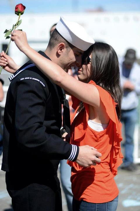 Guns and Military Machinist's Mate Fireman Alessandro Caruso stationed aboard the aircraft carrier USS John C. Stennis (CVN 74) kisses his girlfriend during their homecoming to Naval Station Kitsap in Bremerton, Wash. John C. Stennis is returning from an eight-month deploy