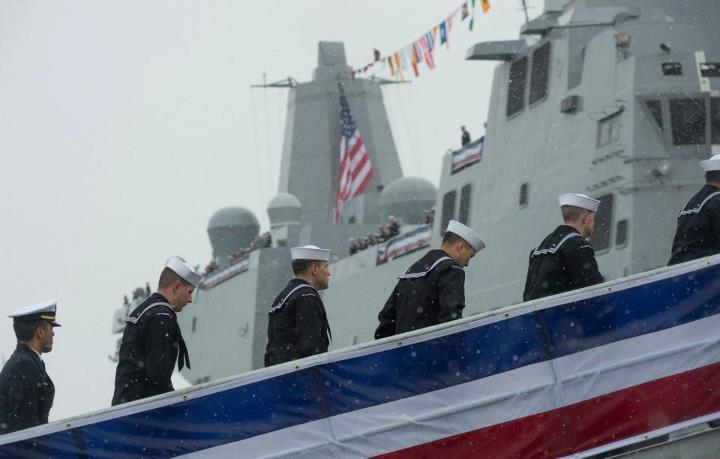 Guns and Military Crew members go aboard to bring the ship to life during the commissioning of the San Antonio-class amphibious transport dock ship USS Anchorage (LPD 23) at the Port of Anchorage. More than 4,000 people gathered to witness the ship's commissioning in its n