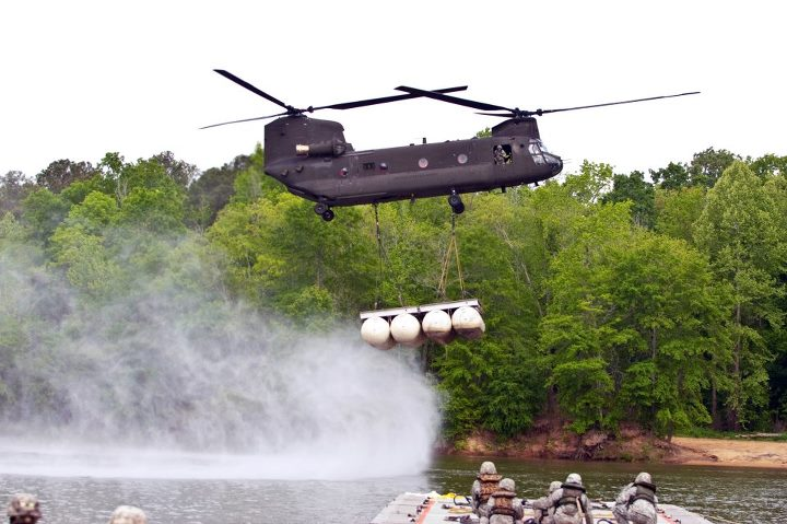 Guns and Military A CH-47 Chinook slows to a hover as it prepares to lower a segment of the Lightweight Modular Causeway System into the Chattahoochee River March 24 at US Army Fort Benning. Soldiers from 362nd Engineer Company, 11th Engineer Battalion, then assembled the
