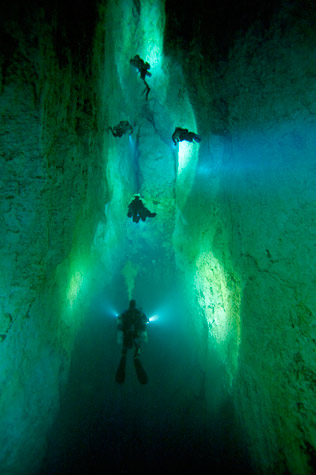 Scuba In Stargate, a blue hole on Andros Island, divers illuminate North Passage.