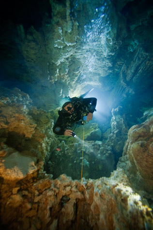 Scuba Through a halo of dive lights, Kenny Broad ascends a deep shaft in Dan's Cave on Abaco.