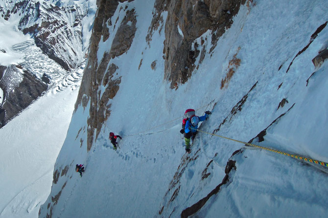 Climbing With crampons, ice axes, and ropes they previously fixed, the climbers traverse west on the edge of the North Ridge