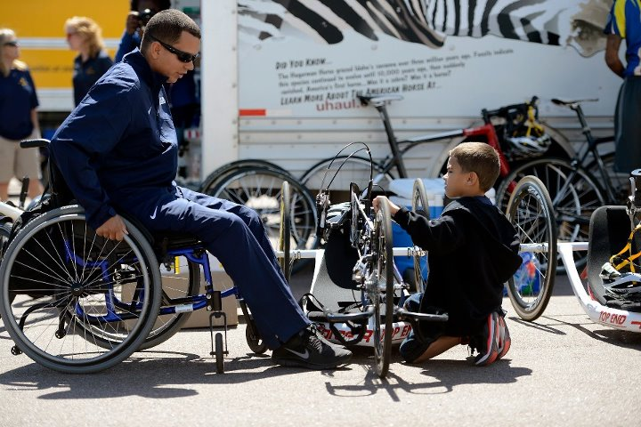 Guns and Military Navy Petty Officer 2nd Class Javier Rodriguez spends some time with his son, Eddier, 6, before the 2013 Warrior Games cycling competition near the U.S. Air Force Academy Stadium in Colorado Springs, Colo., May 12. From May 11-16, more than 200 wounded, il