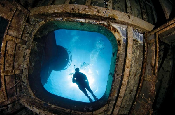 Scuba Brooke Morton peers into a hatch at the bow of ex-USS Kittiwake