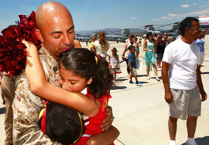 "Guns and Military Group Hug  Staff Sgt. Natividad Herrera, a helicopter mechanic with Marine Medium Helicopter Squadron 364 ""Purple Foxes,"" holds his daughters for the first time in eight months during a homecoming ceremony aboard Marine Corps Air Station Camp Pendleton, C"