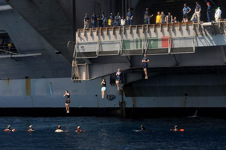 Guns and Military NORTH ARABIAN SEA (May 12, 2013) Sailors jump from  an aircraft elevator during a swim call aboard the aircraft carrier USS Dwight D. Eisenhower (CVN 69). Dwight D. Eisenhower is deployed to the U.S. 5th Fleet area of responsibility promoting maritime sec