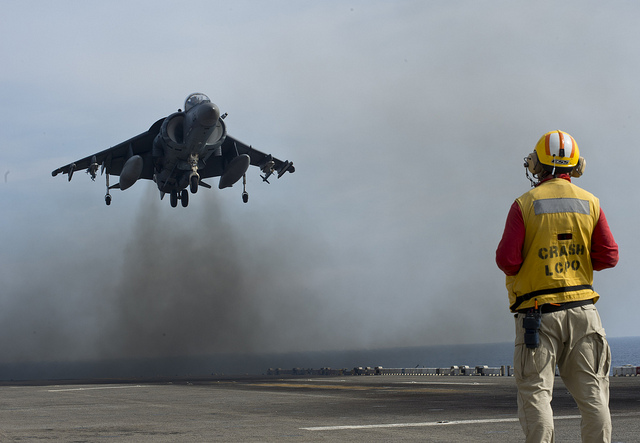 Guns and Military Chief Aviation Boatswain's Mate (Handling) Christopher Carpenter stands by as an AV-8B Harrier jet aircraft,