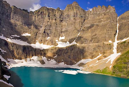 Camp and Hike Looking northwest, Glacier National Park's Iceberg Lake sits at the base of Iceberg Peak's cliffs