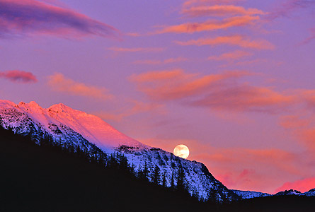 Camp and Hike A wintery full moon rises over Cloudcroft peaks in Glacier National Park.