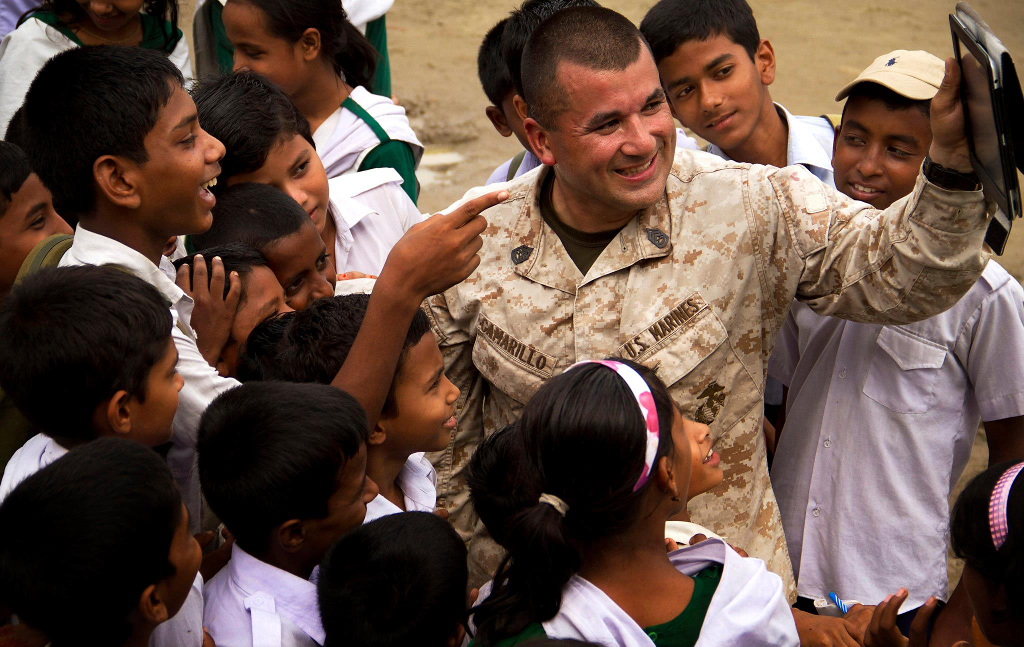 Guns and Military Marine Wing Support Squadron 171 (MWSS-171) Marine Gunnery Sgt. Burney Camarillo, safety staff non-commissioned officer in charge, shows a video of his daughter on his iPad to Bengali schoolchildren in Dhaka, Bangladesh, Sept. 3, 2012.