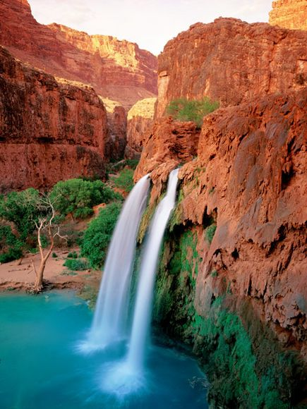 Camp and Hike The twin streams of Havasu Falls splash down into a turquoise pool. The falls are located on the Havasupai Indian Reservation, which lies just outside Grand Canyon National Park