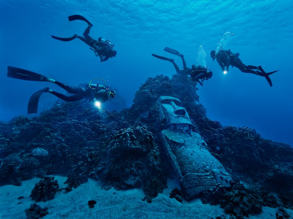 Scuba Picture of divers exploring a reef with fake moai off of Easter Island