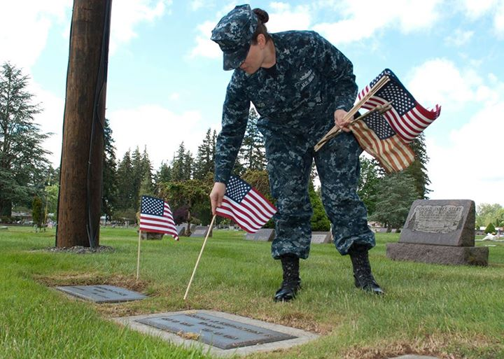 Guns and Military Electronics Technician 1st Class Tracy Rico places an American flag at a gravesite at the Marysville Cemetery in Washington during a CPO 365 community relations project on Thursday. During the event, Sailors maintained graves of veterans at the cemetery i