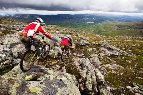 MTB John Alm Högman and Linus Sjöholm ride the slippery rocks at the top of the mountain biking park at Mount Åre, a popular skiing and biking area in Jämtland, Sweden