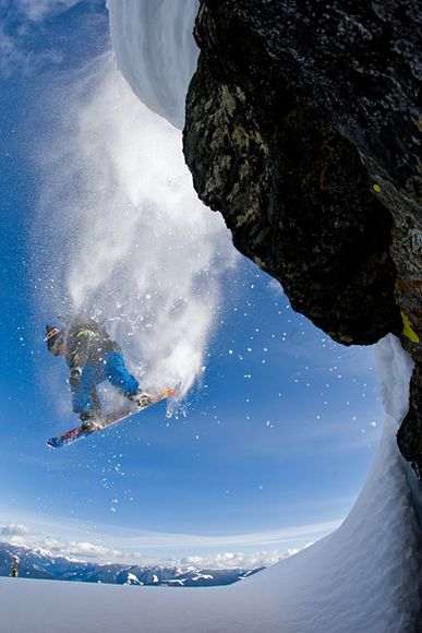 Snowboard Snowboarder Travis Rice flies off a cliff in the Kootenay Mountains, British Columbia, Canada