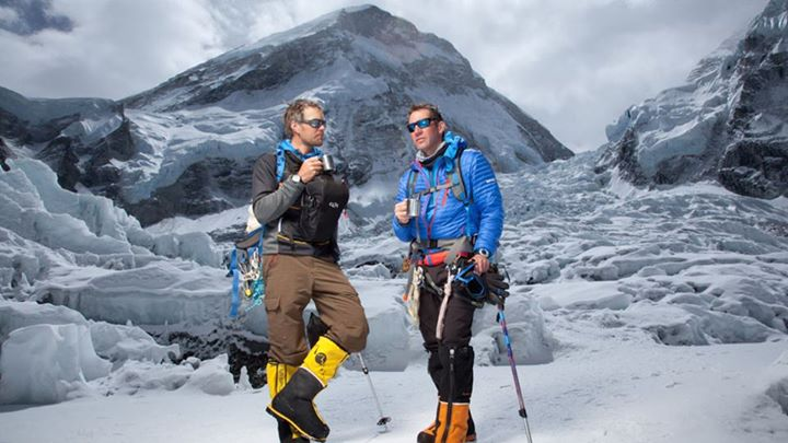 Camp and Hike Tea Time: Jake Norton (left) and Brent Bishop are met by their camp cook near the bottom of the icefall with hot drinks. Everest's West Ridge rises directly above them.