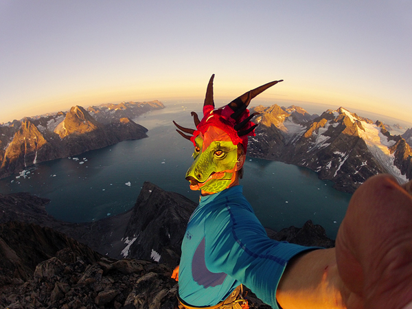 Climbing Libecki, wearing a dragon mask, is seen on the summit of Greenland's 4,610-foot Ataatap Tower (Daddy's Tower) after making the first ascent—on sight, free solo—in three hours.