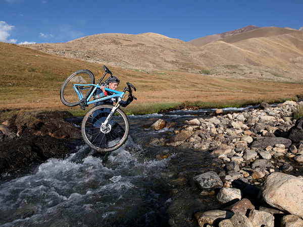 MTB Picture of Shannon Galpin carrying a bike across a river, Afghanistan