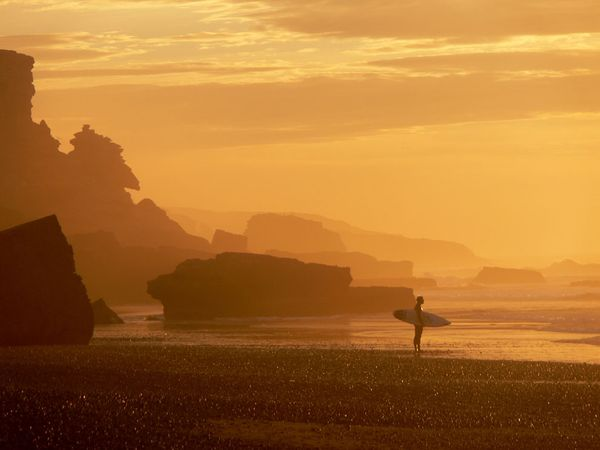 Surf Surfer on beach, sunset, Tamri Plage, Morocco
