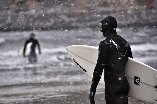 Surf Surfer stands near shore, snow falls down, Hoddevik, Norway