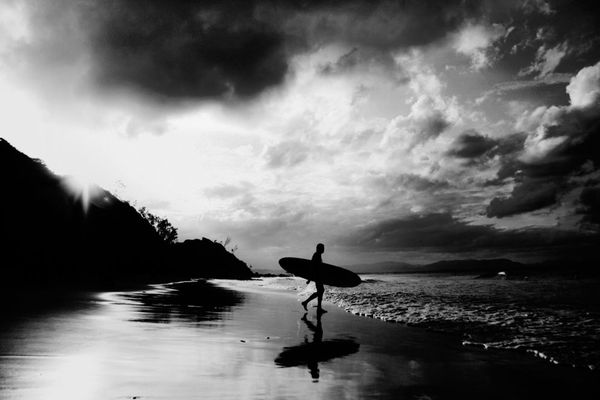 Surf Surfer walking on beach silhouetted by the sun
