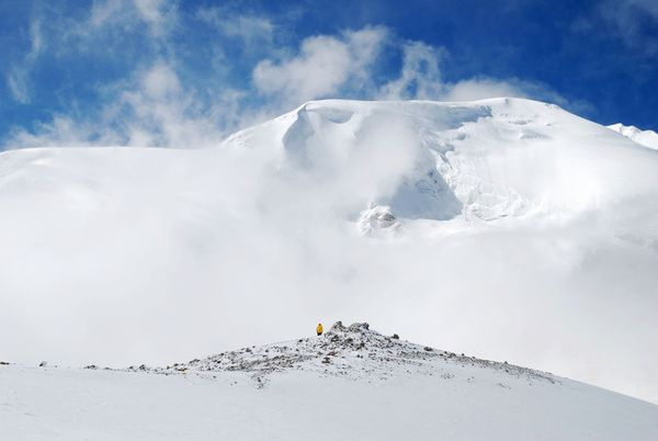 Climbing Man stands in snow looking up at Trong La Pass in Nepal