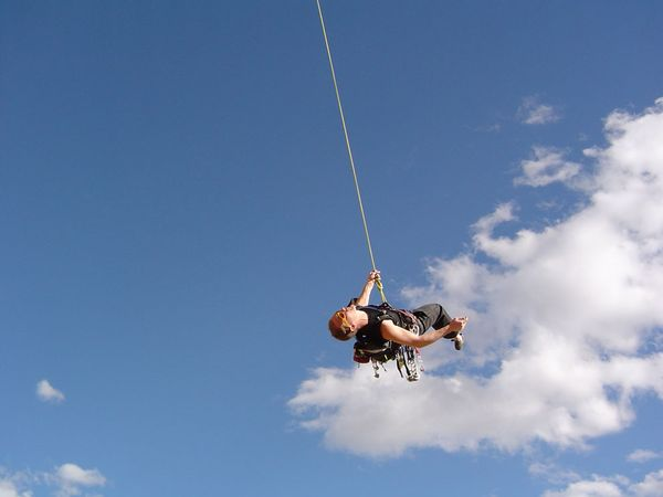 Climbing Man swings on rope in air